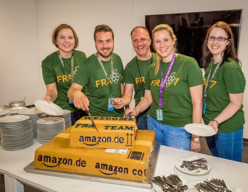 """Ein zweistöckige Torte in Form von Päckchen trägt schwarze Beschriftungen mit """"amazon.de"""" und """"Fra7 Team"""". Die Torte steht auf einem Tisch auf dem ebenfalls viele Kuchenteller und Dessertgabeln angeordnet wurden. Fünf Mitarbeiter mit grünen T-Shirts sind um die Torte versammelt. Alle lächeln in die Kamera. Einer von ihnen: der Standortleiter. Er ist im Begriff, die Torte anzuschneiden."""