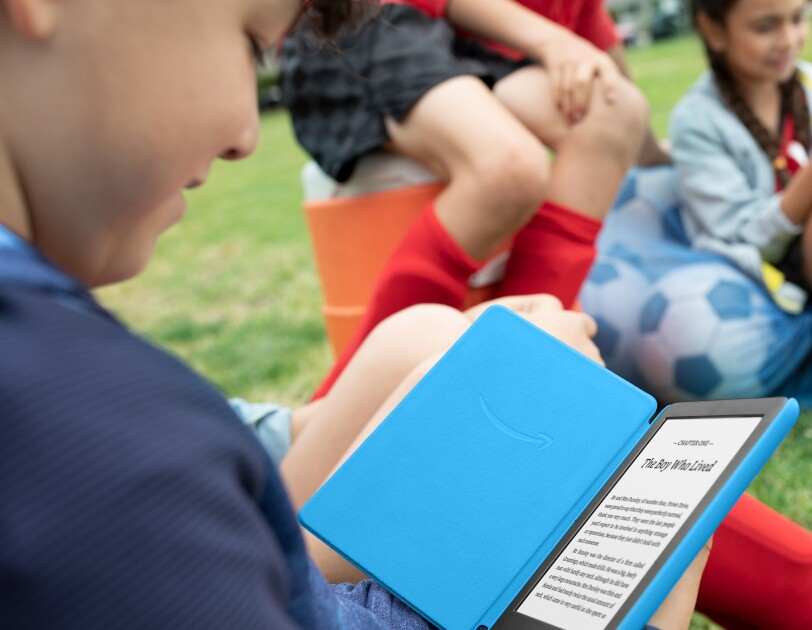 Child reading a book at the park on the Amazon Kindle Kids Edition