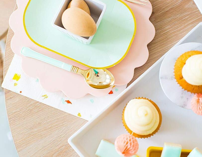 A white melamine tray sits on a light wood table. On the tray sits a small yellow dish of ice shortbread cookies, a small cupcake, and a small marble-looking cupcake stand. To the left of the tray, a small, scalloped plate sits under a gold-rimmed aqua plate, which holds a small striped white dish.