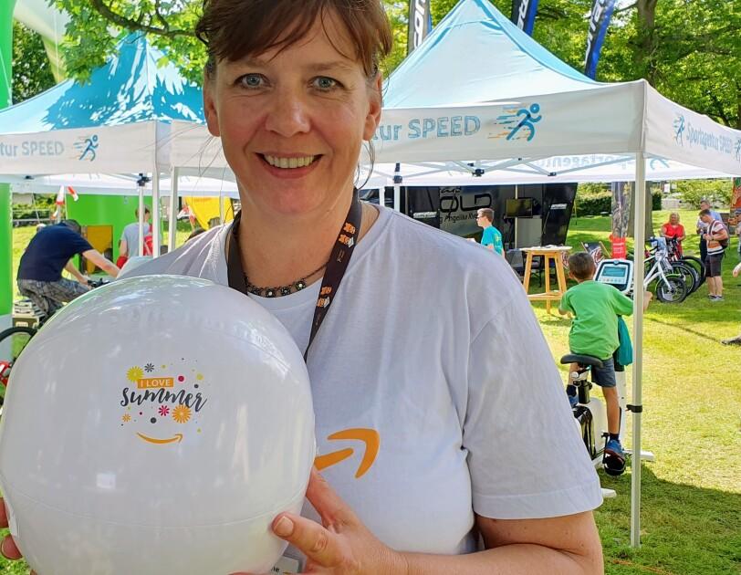 """Eine lächelnde Frau im Amazon T-Shirt hält einen weißen Luftballon auf dem """"I love summer"""" zu lesen ist"""