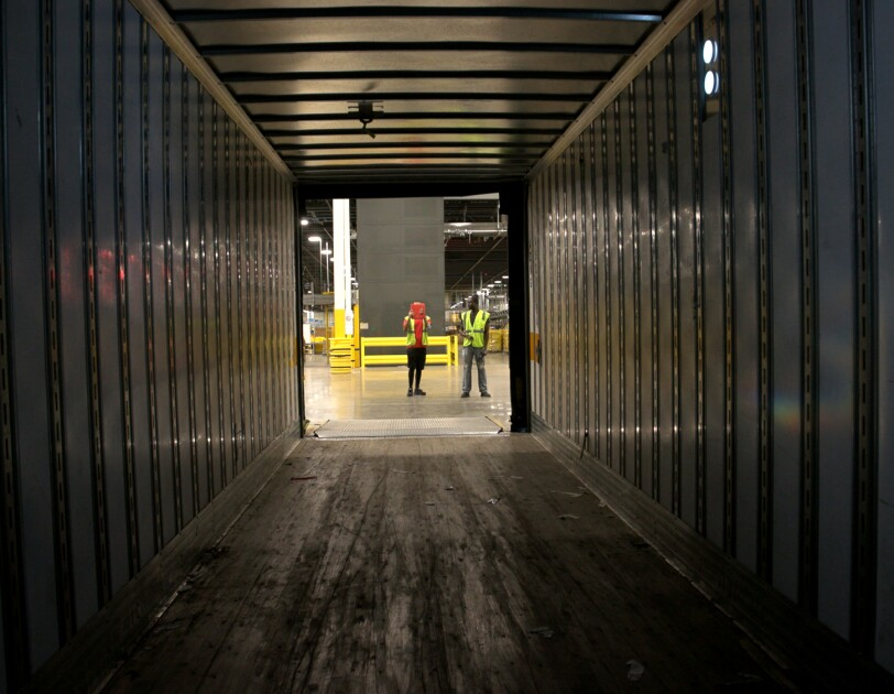 Photograph from inside an empty cargo trailer. Two people in safety vests are in the background of the image.