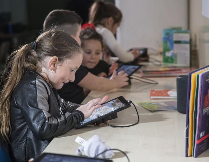 Bambini giocano con i tablet Fire messi a disposizione da Amazon per la sala multimediale della Biblioteca di Scampia