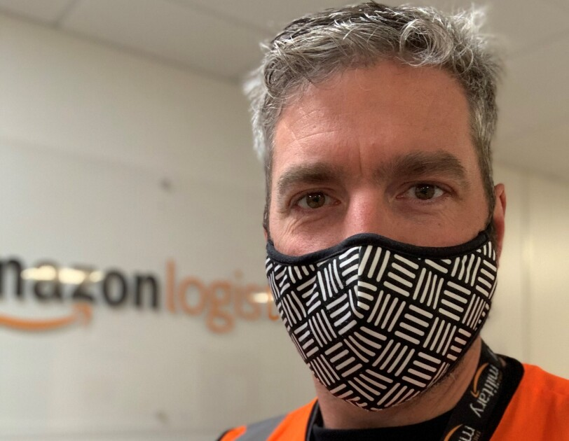 Amazon employee wearing  a mask and orange high vis vest