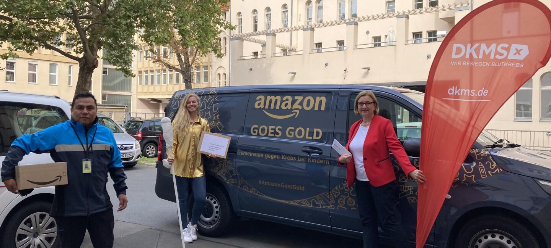 """Amazon übergibt eine Spende an eine Vertreterin des DKMS. Die Vertreterin, eine Amazon Mitarbeiterin und ein Amazon Lieferpartner stehen vor einem mit """"Amazon goes gold"""" beschrifteten blauen Liefervan."""