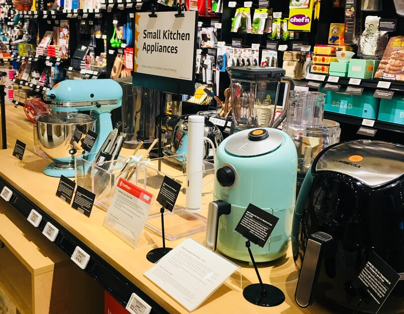 "A display area in Amazon 4-star. A display area of Small Kitchen Appliances has a KitchenAid Mixer, Sous Vide, air fryer, food processor and more. Behind the display are sections for ""Cooks' Tools,"" ""Kitchen Gifts,"" ""Bar and Party Supplies,"" ""Quirkly Kitchen Gifts,"" and more."