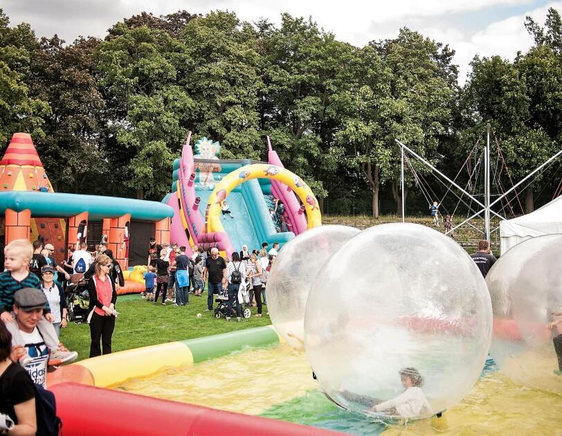Verschiedene Spielstationen auf dem Spielfest: Man sieht Besucher und riesige Ballon, die auf einem aufblasbaren Schwimmbecken treiben, Im Balloninneren sind Kinder.