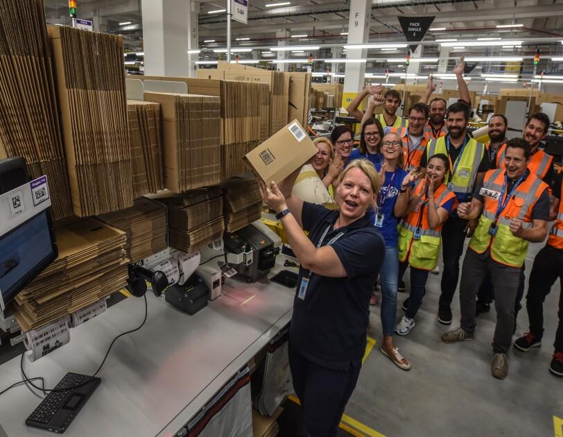 Eine Mitarbeiterin hält ein Päckchen hoch.