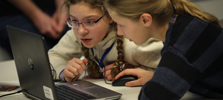 Girls and Boys Day bei Amazon. Zwei junge Mädchen sitzen konzentriert vor dem Laptop.