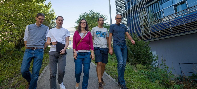 Fünf Personen - vier Männer und eine Frau mit pinkem Pulli in der Mitte - gehen einen Hang hinunter