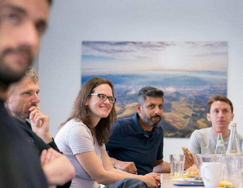 Betty Mohler, umgeben von ihren Kollegen, macht ein fröhliches Gesicht