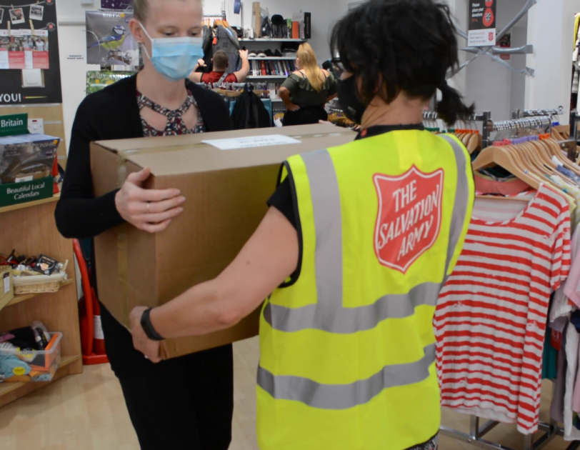 Salvation Army employee recieving a box of FBA donations in a Salvation Army story.