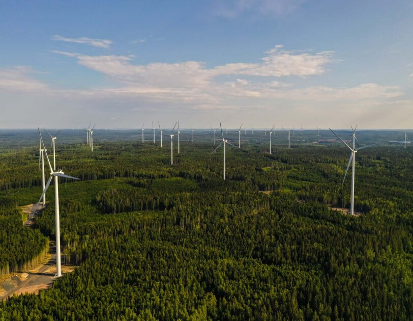 Aerial photo of wind farm turbines spread across the forest in Bäckhammar, Sweden.