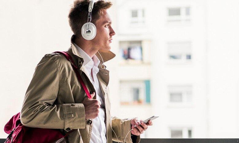 A stylishly dressed man listens to audio from his smartphone via headphones