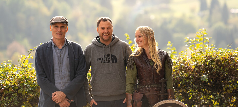Zwei Männer und eine Frau lachen in die Kamera. Im Hintergrund ist eine grüne Hecke.
