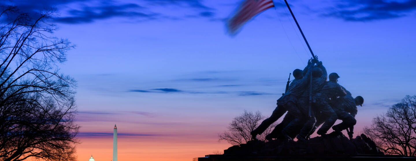 US Marine Corps War Memorial in front of a sunset with the Lincoln Memorial, Washington Monument, and US Capitol dome receding toward the horizon