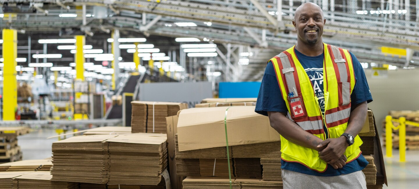 An Amazon associate stands, facing the camera, from within an Amazon fulfillment center.