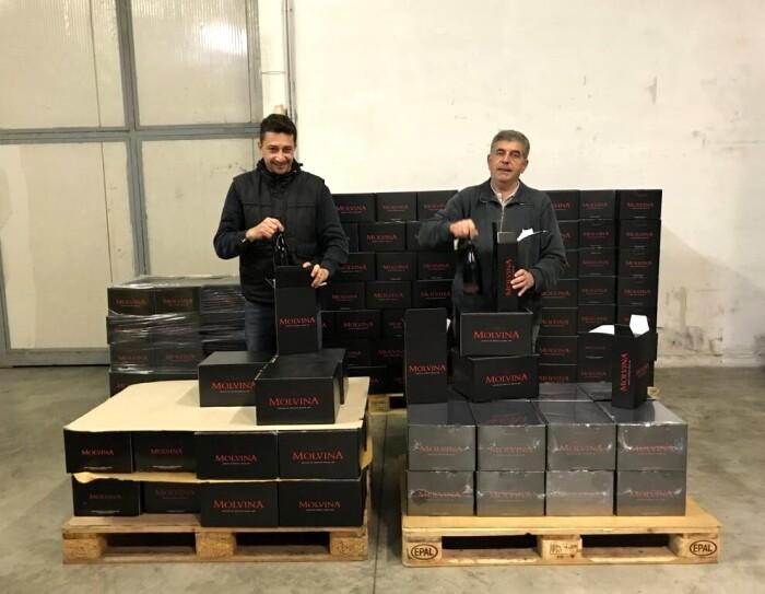 Due uomini in un capannone di fronte a due pallet con delle casse di vino in scatole nere.