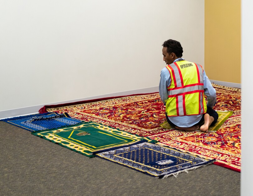 A man kneels on a small rug placed atop a larger rug in a carpeted room with blank walls. Three small rugs are placed at the edge of the larger rug.