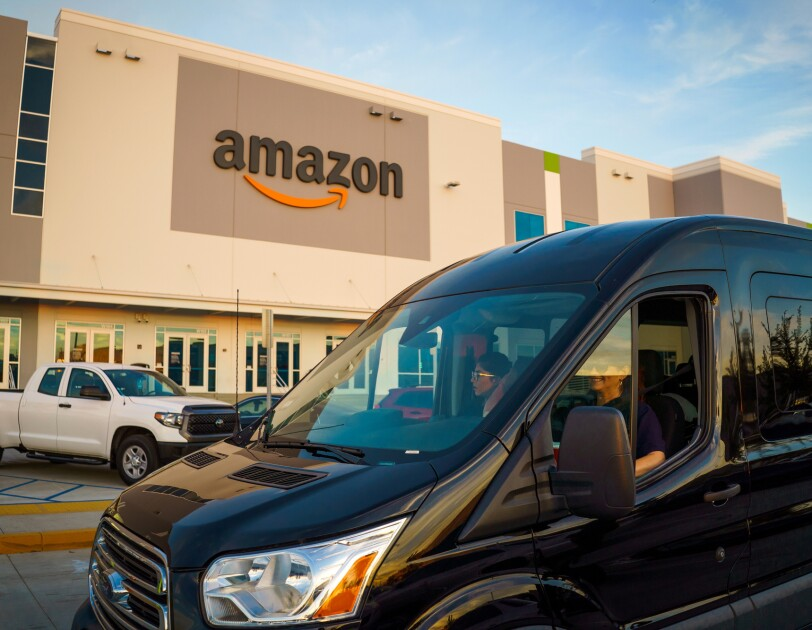 A shiny black van drives through a parking lot flanked by a building bearing the Amazon logo.