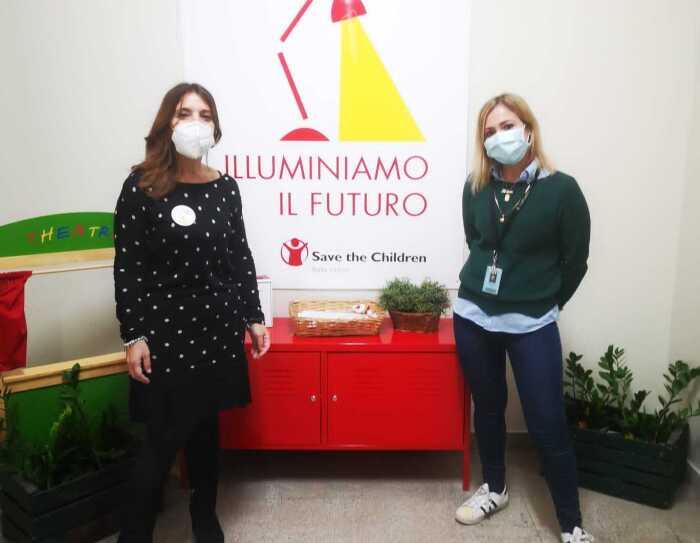 Due volontarie del punto luce di Save the Children di Catania posano davanti ad un cartellone con la scritta 'Illuminiamo il futuro'.