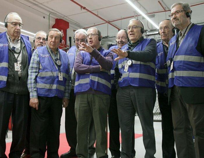 Un grupo de ingenieros jubilados durante una visita al centro logístico. Todos ellos visten con chaleco azul.