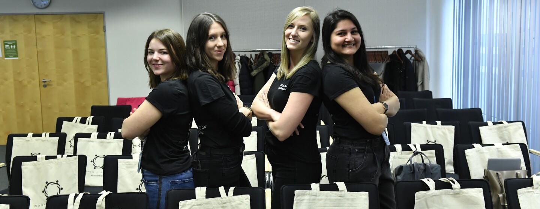 Eine Gruppe Mädchen in schwarzen IWD-T-Shirts posiert für die Kamera