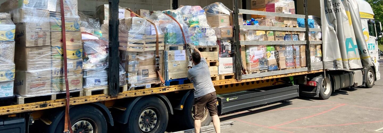 Ein Mann lädt Hilfsgüter von einem Lkw.