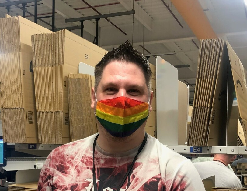 Dean Barnes, an associate at Amazon's fulfilment centre in Durham, pictured at his packing station wearing a rainbow coloured face mask.
