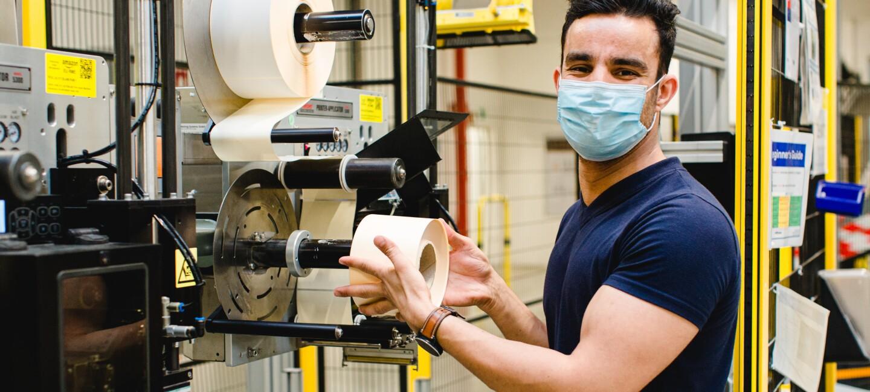 Ein junger Mann mit Maske an einer Etikettiermaschine