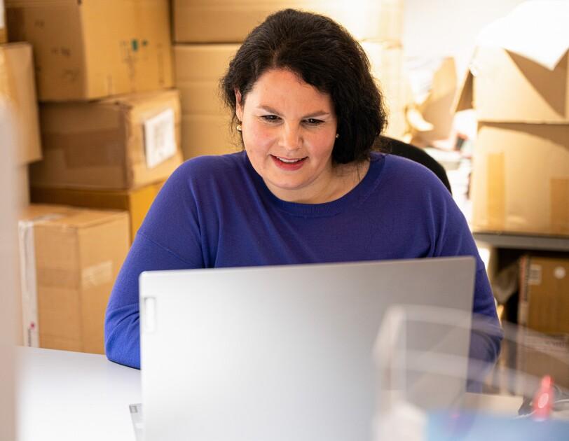 Eine Frau in einem blauen Pullover schaut in einen grauen Laptop.