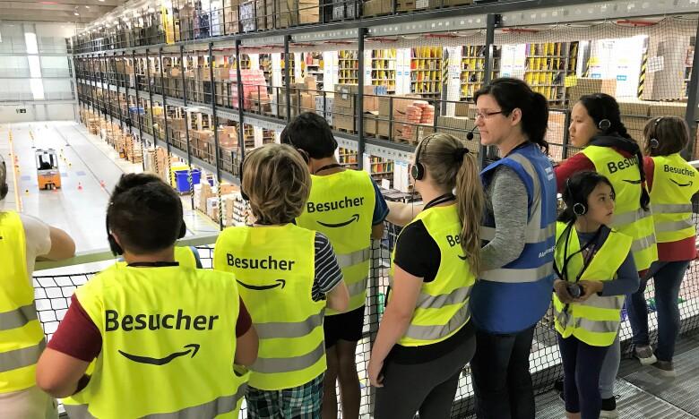 Eine Gruppe von KIndern mit gelben Besucherwesten blickt zusammen mit einer Amazon Mitarbeiterin in blauer Sicherheitsweste von einer Balustrade auf die Logistikhalle unter ihnen.