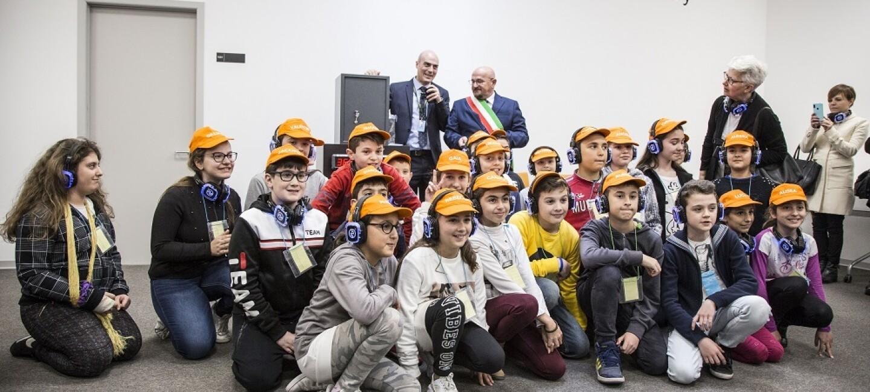 Bambini della scuola elementare seduti in terra con general manager Amazon e sindaco di Torrazza Piemonte per la cerimonia della capsula del tempo