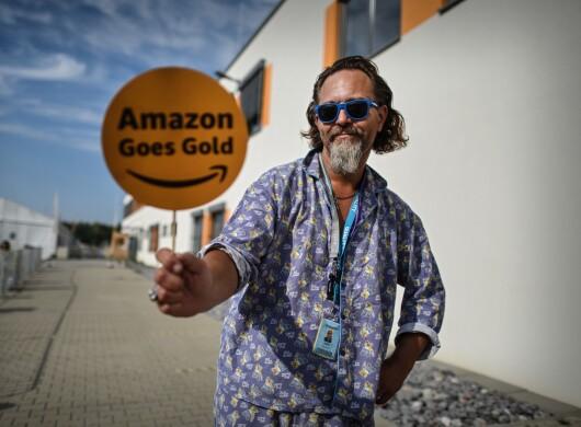 Amazon Mitarbeiter im Schlafanzug mit Amazon Goes Gold Schild