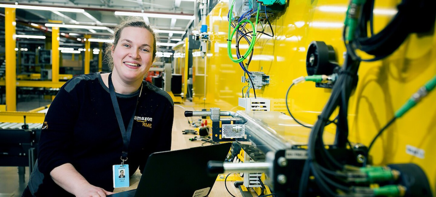 Amazon Appretice, Nicola Elliott, leaning at her workbench with with her laptop. She is in the Bolton Fulfilment Centre next to a yellow wall with lots of wires and equipment attached to it.