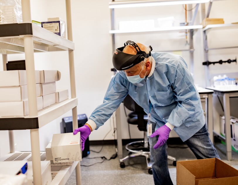 A man wearing protective gear, including a mask, gloves, and face shield, places a box onto a shelf in a laboratory setting.
