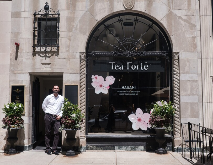 """A man in a white button-down shirt stands in front of a storefront with the words """"Tea Forté"""" on it."""