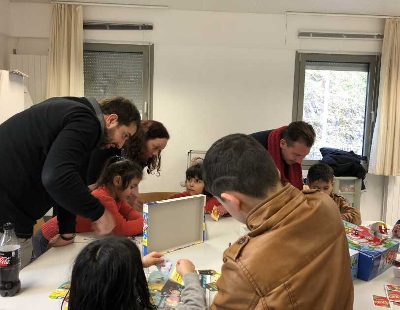 Amazonians play board games with the children at Marianthel Foyer, a Luxembourg refugee camp
