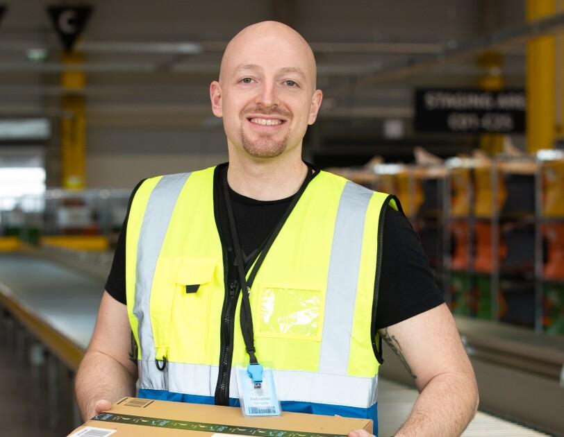 Ein Mann in Sicherheitsweste mit einem Päckchen in der Hand.