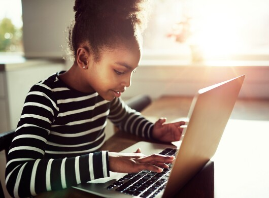 A young girl sits at a table using her laptop.