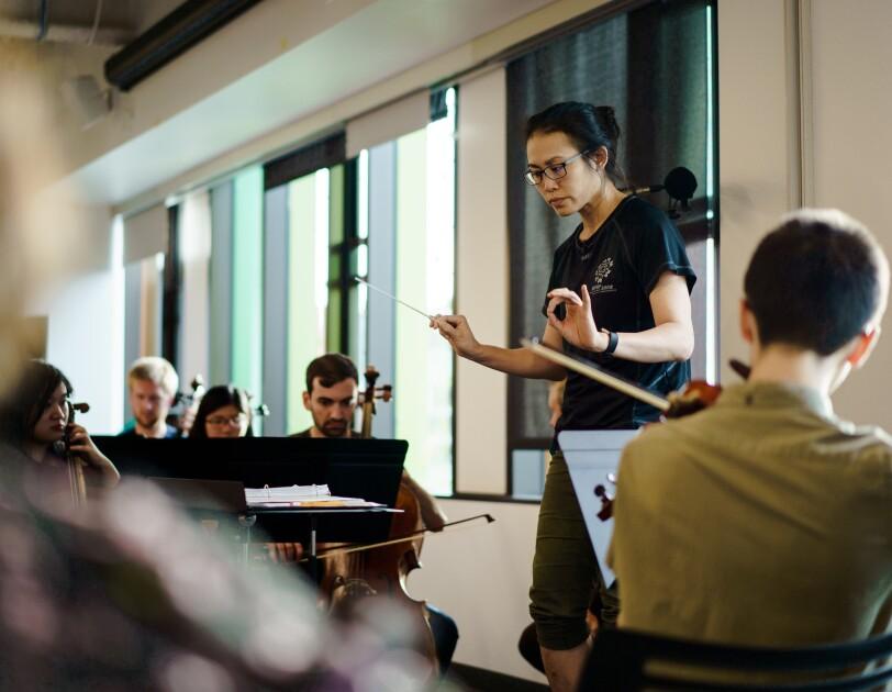 A conducutor leads musicians in a rehearsal.