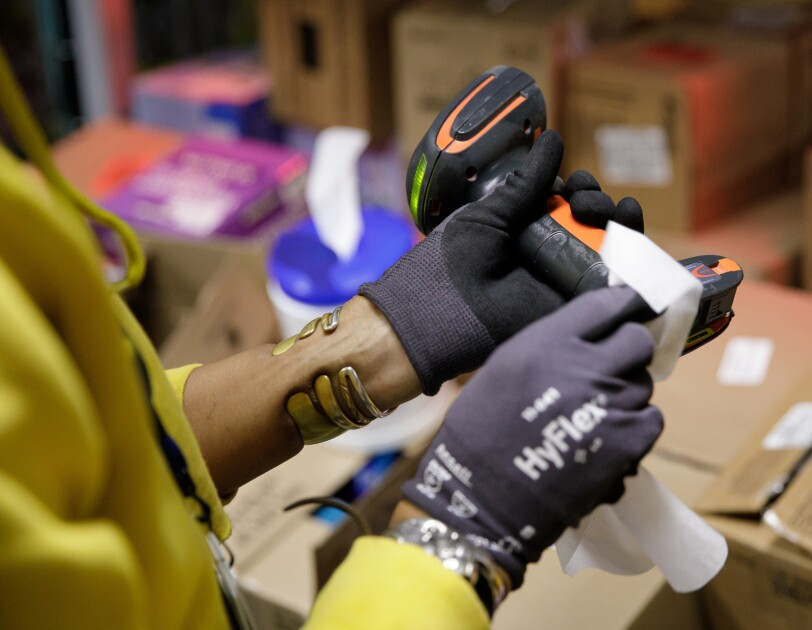 A person wearing gloves wipes down a device.