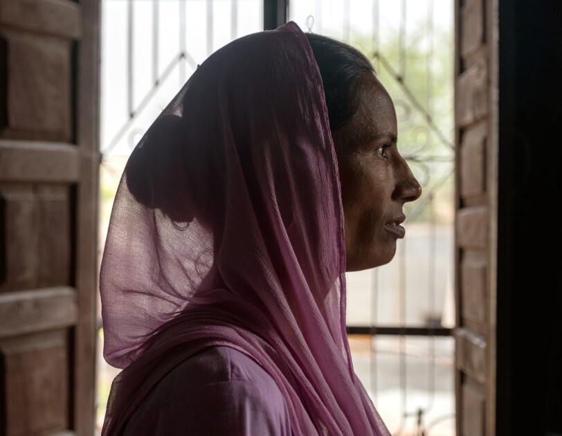 Woman in a pink headscarf in profile. Open double doors are in the background.