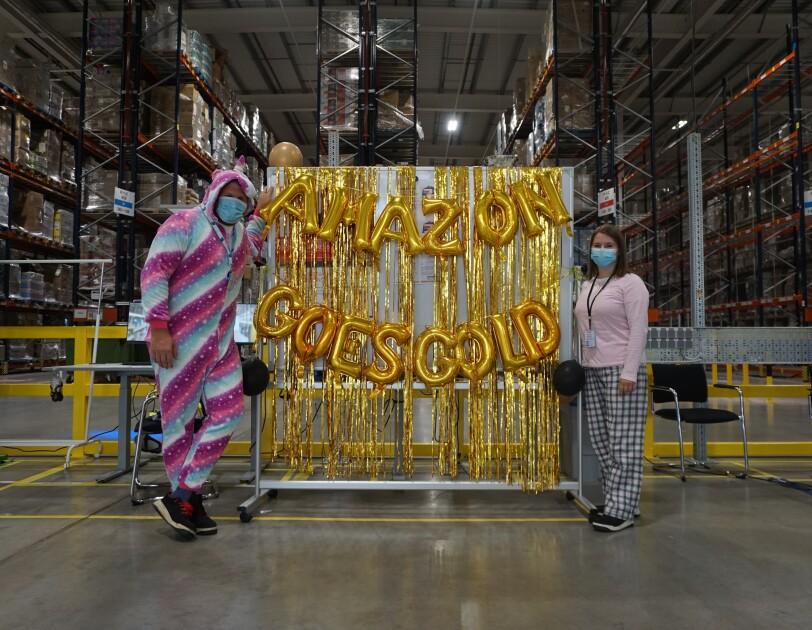 """Zwei Mitarbeiter:innen im Pyjama vor einem Schild, auf dem """"Amazon goes gold"""" steht."""