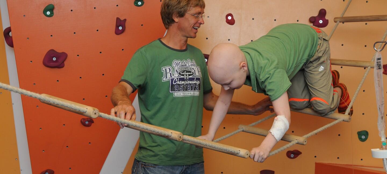 Der erkrankte Fabian klettert mit Hilfe des Sporttherapeuten über eine Hängeleiter.