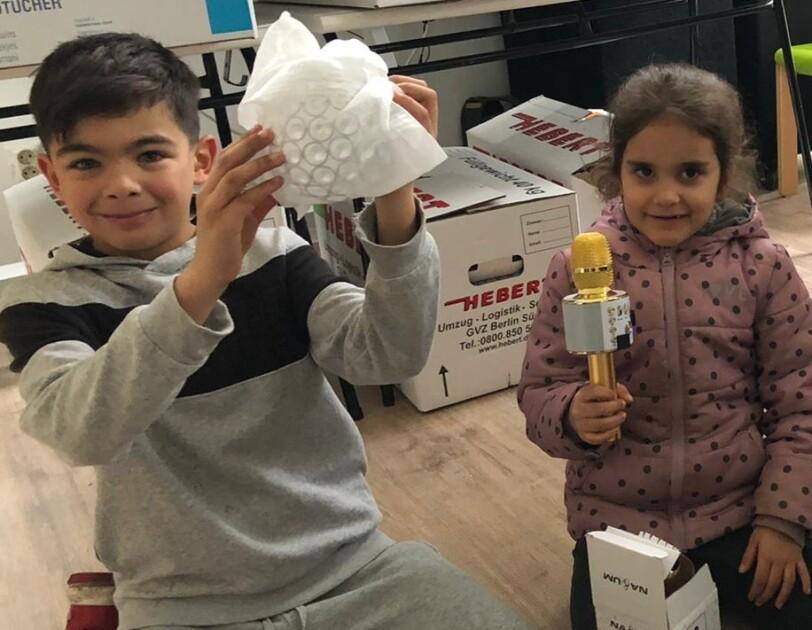 Ein Junge hält ein halb ausgepacktes Geschenk, während sich ein Mädchen über ein goldenes Mikrophon freut.