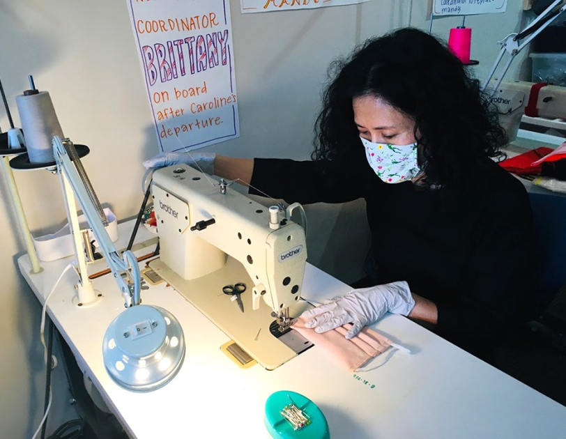 A woman works at a sewing machine.