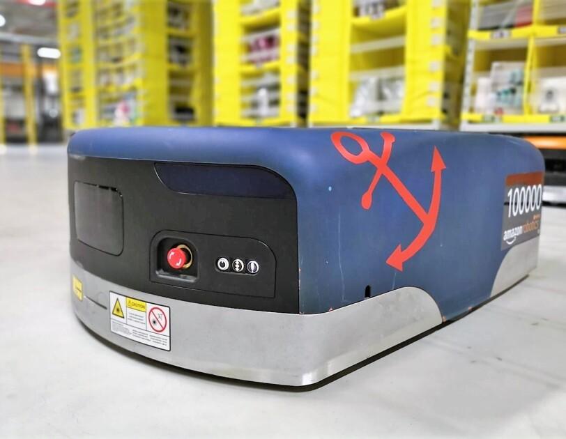"""Auf dem Boden einer Lagerhalle sieht man einen blauen Amazon Transportroboter. Auf der rechten Seite wurde ein roter Anker aufgeklebt und ebenfalls rechts steht die kennzeichnung """"100000 amazon robotics""""."""
