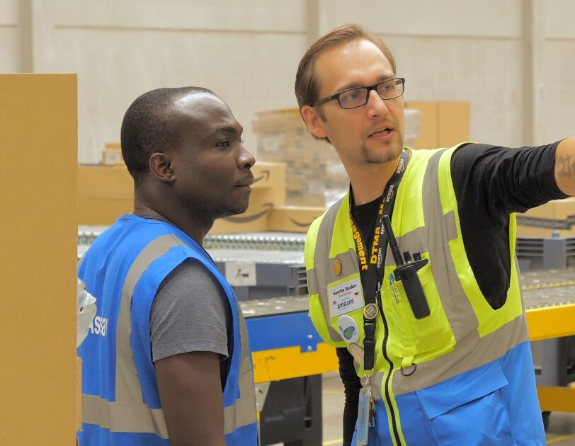 Sascha (rechts) im Gespräch mit einem Mitarbeiter. Beide tragen Sicherheitswesten.