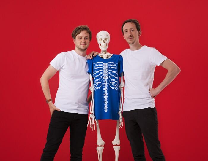 Ed Barton e Ben Kidd, fondatori di Curiscope. I due ragazzi, in t-shirt bianca e pantaloni nero, abbracciano uno scheletro con una t-shirt blu. Sfondo rosso.