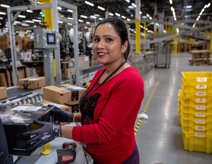 An Amazon associate holds a product near a conveyor belt. Tools sit on the countertop near her. She wears a red long-sleeve tee shirt and work gloves as she works at a Columbus, Ohio fulfillment center, CMH1